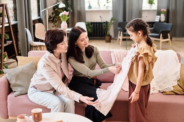 Adorable fille essayant une nouvelle robe devant sa mère et sa grand-mère