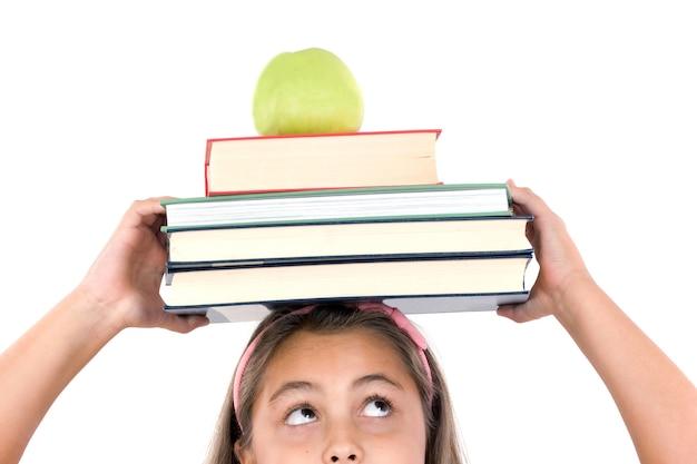 Adorable fille étudie avec des livres et pomme dans la tête
