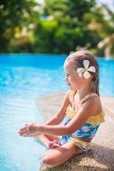 Adorable fille avec une fleur derrière son oreille se trouve près de la piscine