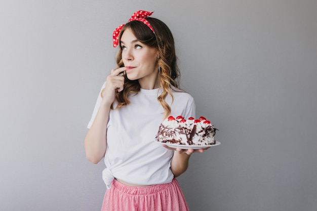 Adorable fille frisée dégustant un gâteau aux fraises. tir intérieur d'un modèle féminin romantique avec un ruban rouge dans les cheveux tenant une tarte savoureuse.