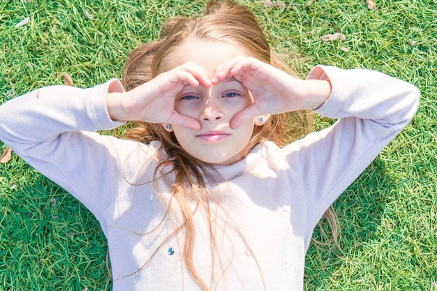 Adorable fille heureuse sur l'herbe verte