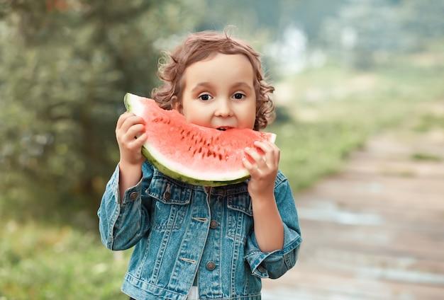 Adorable fille heureuse mange une tranche de pastèque mûre à l'extérieur.