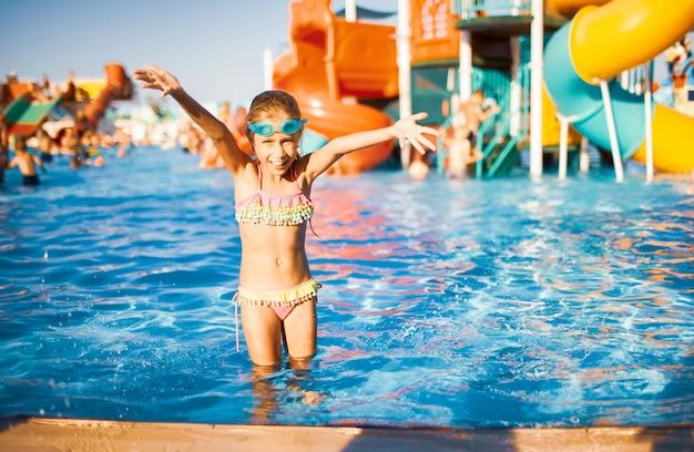 Une adorable fille à lunettes bleues pour nager et un maillot de bain lumineux se tient dans une piscine avec de l'eau claire près du côté, et éclabousse tout en levant les mains