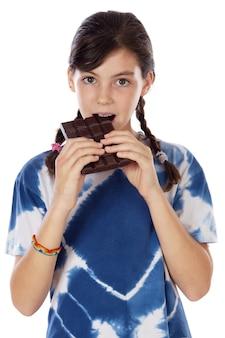 Adorable fille mangeant du chocolat sur fond blanc
