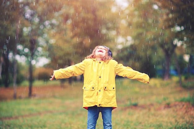 Adorable fille en manteau de pluie jaune jouant sous la pluie dans le parc en automne