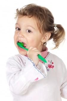 Adorable fille nettoyant les dents sur fond blanc