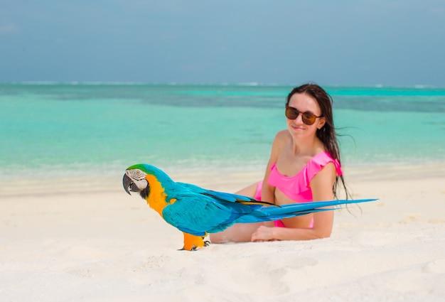 Adorable fille à la plage avec perroquet coloré