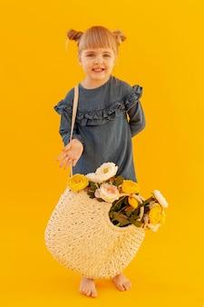 Adorable fille portant un panier de fleurs
