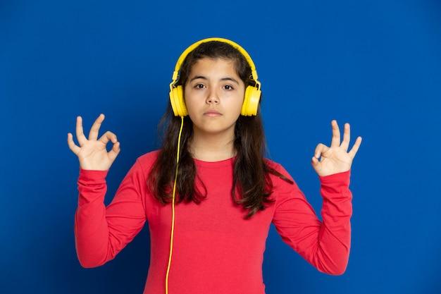 Adorable fille préadolescente avec maillot rouge gesticulant sur mur bleu