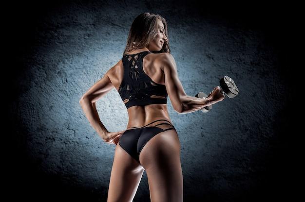 Adorable fille s'entraîne dans la salle de gym. elle soulève les haltères