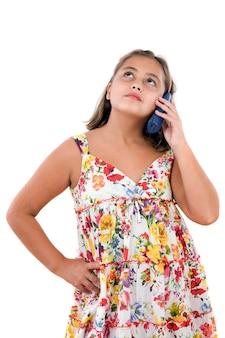 Adorable fille s'exprimant par téléphone sur un fond blanc