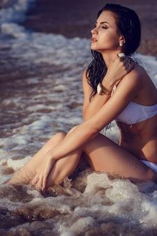 Adorable fille sexy en bikini profitant de l'été. portrait en plein air. vagues de la mer et mousse blanche. coucher de soleil après la pluie sur l'île