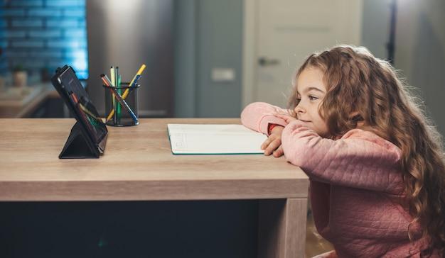 Adorable fille suit des cours en ligne en utilisant une tablette pour écouter le professeur et écrire le sujet