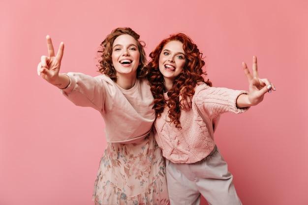 Adorable filles montrant des signes de paix et souriant. photo de studio de deux amis isolés sur fond rose.