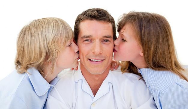 Adorable frères et sœurs embrassant leur père