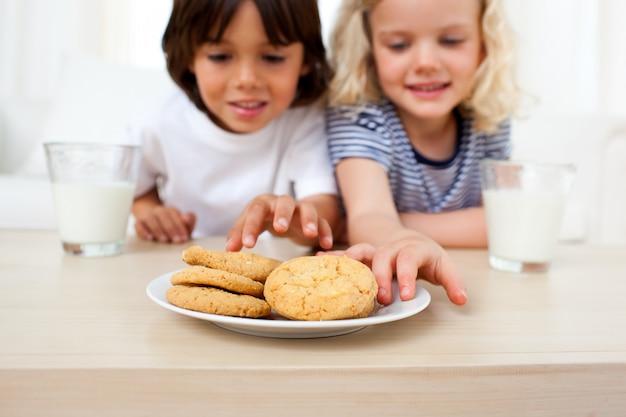 Adorable frères et sœurs manger des biscuits