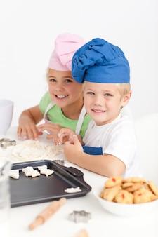 Adorable frères et soeurs pétrissant une pâte dans la cuisine