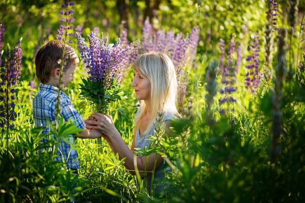 Adorable gamin et maman au parc du printemps, fleurs et cadeaux.