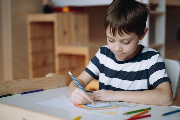 Adorable garçon caucasien d'âge élémentaire dessinant un arc-en-ciel avec des crayons assis au bureau