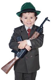 Adorable garçon en costume avec mitrailleuse