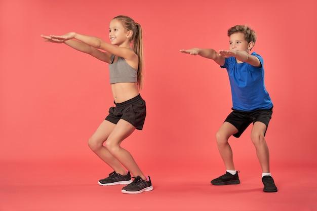 Adorable garçon et fille en tenue de sport faisant des squats en studio