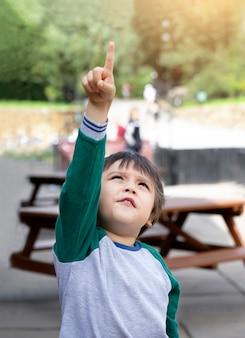 Adorable garçon pointant son doigt vers le ciel avec une lumière brillante du soleil le matin