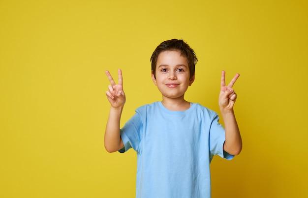 Adorable garçon posant dans l'appareil photo sur fond jaune avec copie espace