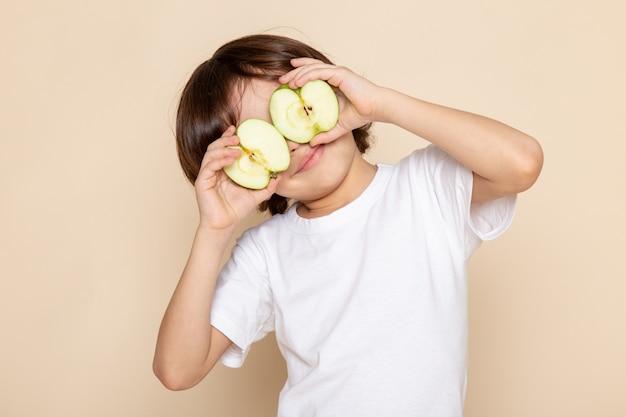 Adorable garçon tenant une pomme verte à moitié coupée sur un bureau rose