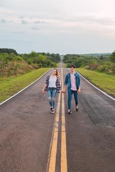 Adorable jeune couple marchant main dans la main sur la route ensemble.