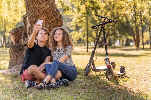 Adorable jeune couple prenant un selfie à l'extérieur
