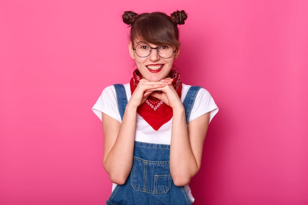Adorable jeune étudiante charmante touchant son menton avec les deux mains, regardant directement la caméra, étant gaie, portant des lunettes rondes élégantes, une salopette en jean, un bandana rouge et un t-shirt blanc.