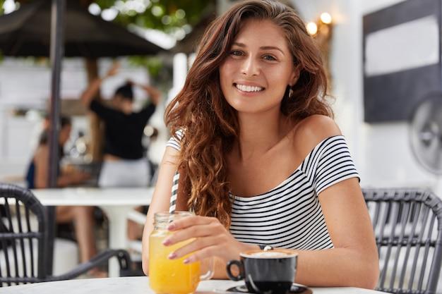 Adorable jeune femme aux cheveux longs foncés, vêtue d'un t-shirt rayé dans un café, boit du jus de fruits frais et de l'espresso.