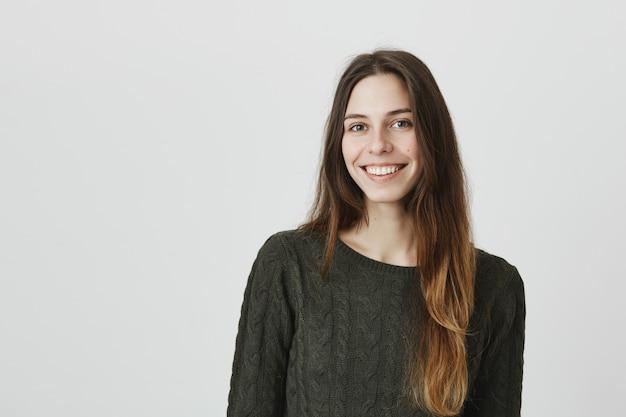 Adorable jeune femme aux cheveux longs, souriant à la caméra