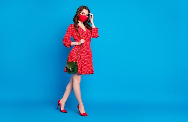 Adorable jeune femme brune en mini robe rouge porter un masque médical posant