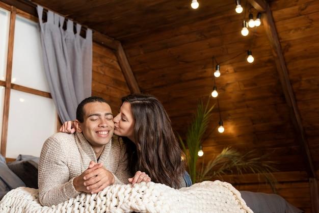 Adorable jeune femme embrasse un homme