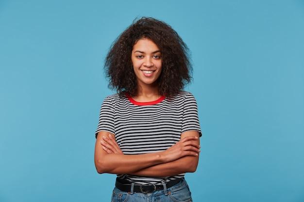 Adorable jeune femme heureuse confiante avec un regard ludique a une coiffure afro en riant souriant contre le mur bleu