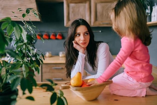 Adorable jeune femme jouant avec sa petite fille drôle en cuisine.