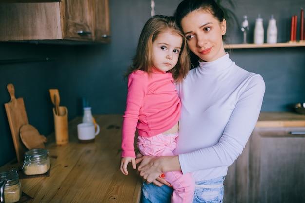 Adorable jeune femme jouant avec sa petite fille drôle dans la cuisine. portrait de jolie mère étreignant, portant et regardant son petit enfant de sexe féminin.