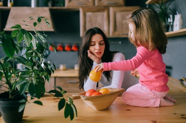 Adorable jeune femme jouant avec sa petite fille drôle dans la cuisine.