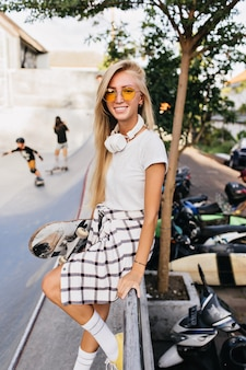 Adorable jeune femme à lunettes de soleil jaunes posant sur fond de rue avec un sourire timide.