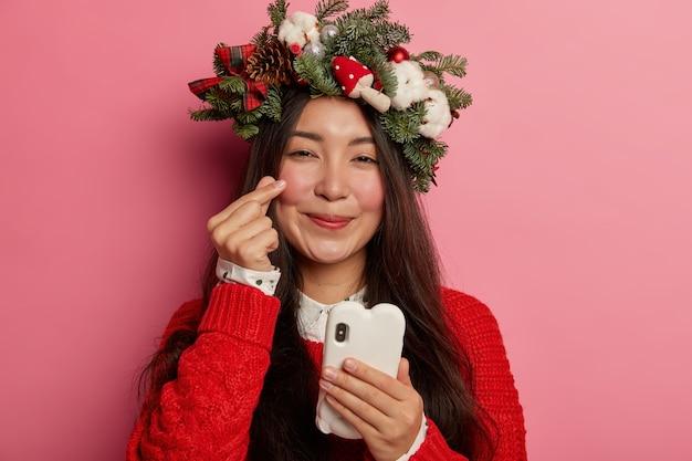 Adorable jeune femme sourit agréablement portant une couronne de fête sur la tête