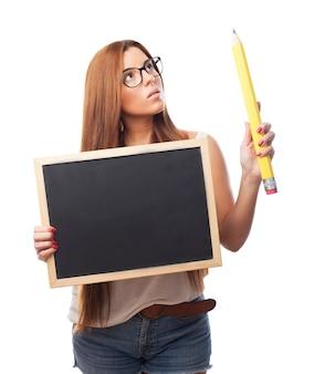 Adorable jeune femme avec tableau noir et un grand crayon