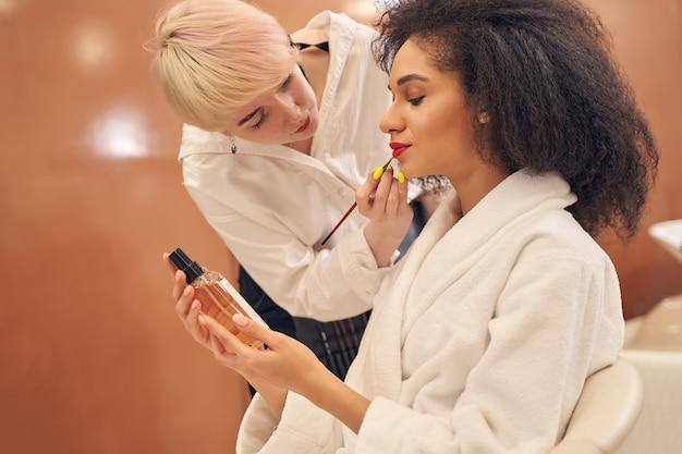 Adorable jeune femme tenant une bouteille de pompe cosmétique tout en visagiste habile utilisant un pinceau et appliquant du rouge à lèvres rouge