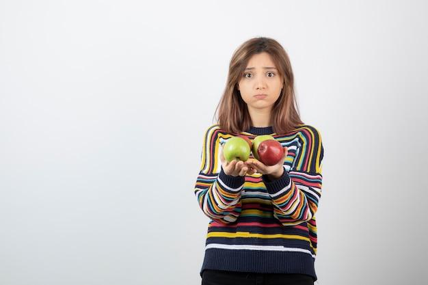 Adorable jeune femme en vêtements décontractés tenant des pommes colorées.
