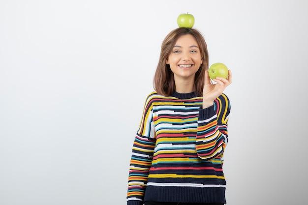 Adorable jeune femme en vêtements décontractés tenant des pommes vertes sur fond blanc.