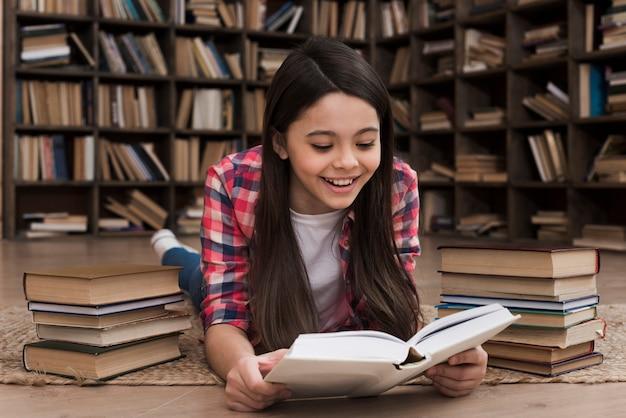Adorable jeune fille étudie à la bibliothèque