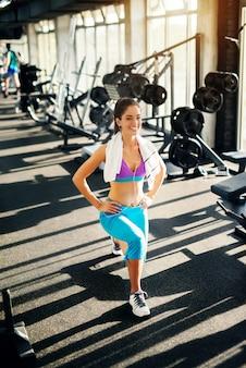 Adorable jeune fille mince faisant des exercices de progression dans la salle de sport tout en ayant une serviette sur le cou.