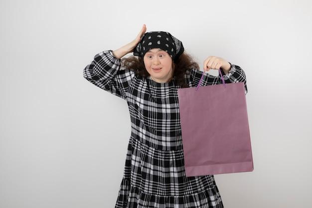 Adorable jeune fille trisomique tenant un sac à provisions.