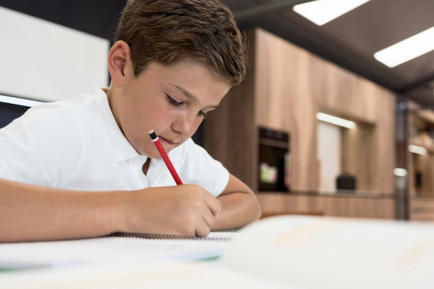 Adorable jeune garçon fait ses devoirs