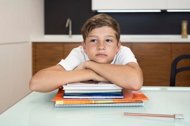 Adorable jeune garçon fatigué après avoir fait ses devoirs
